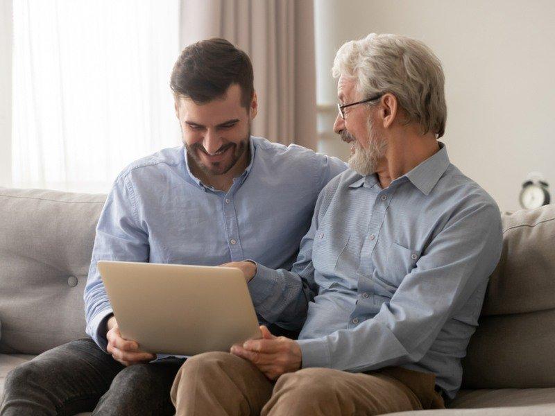 Padre anziano e figlio adulto seduti sul divano mentre usano un laptop