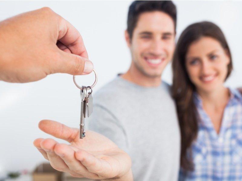 Coppia sorridente a cui viene dato un mazzo di chiavi