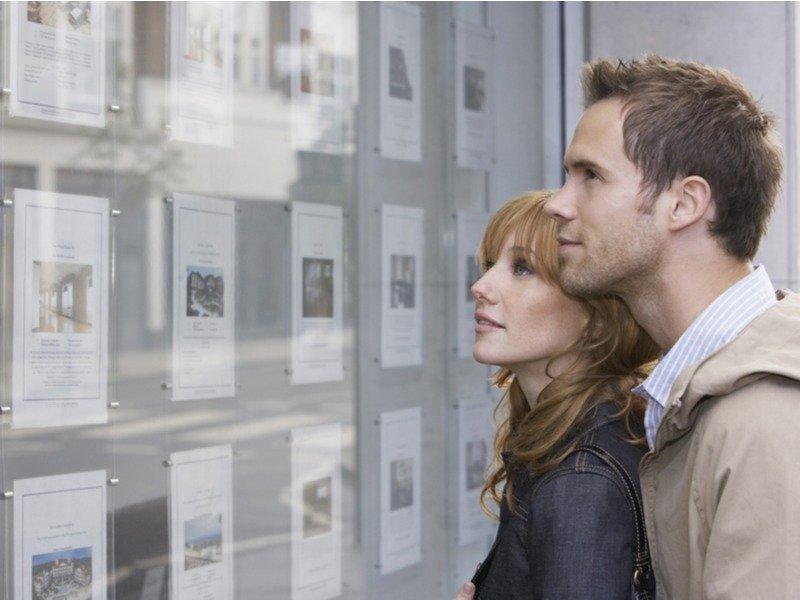 Giovane coppia guarda la vetrina di un'agenzia immobiliare